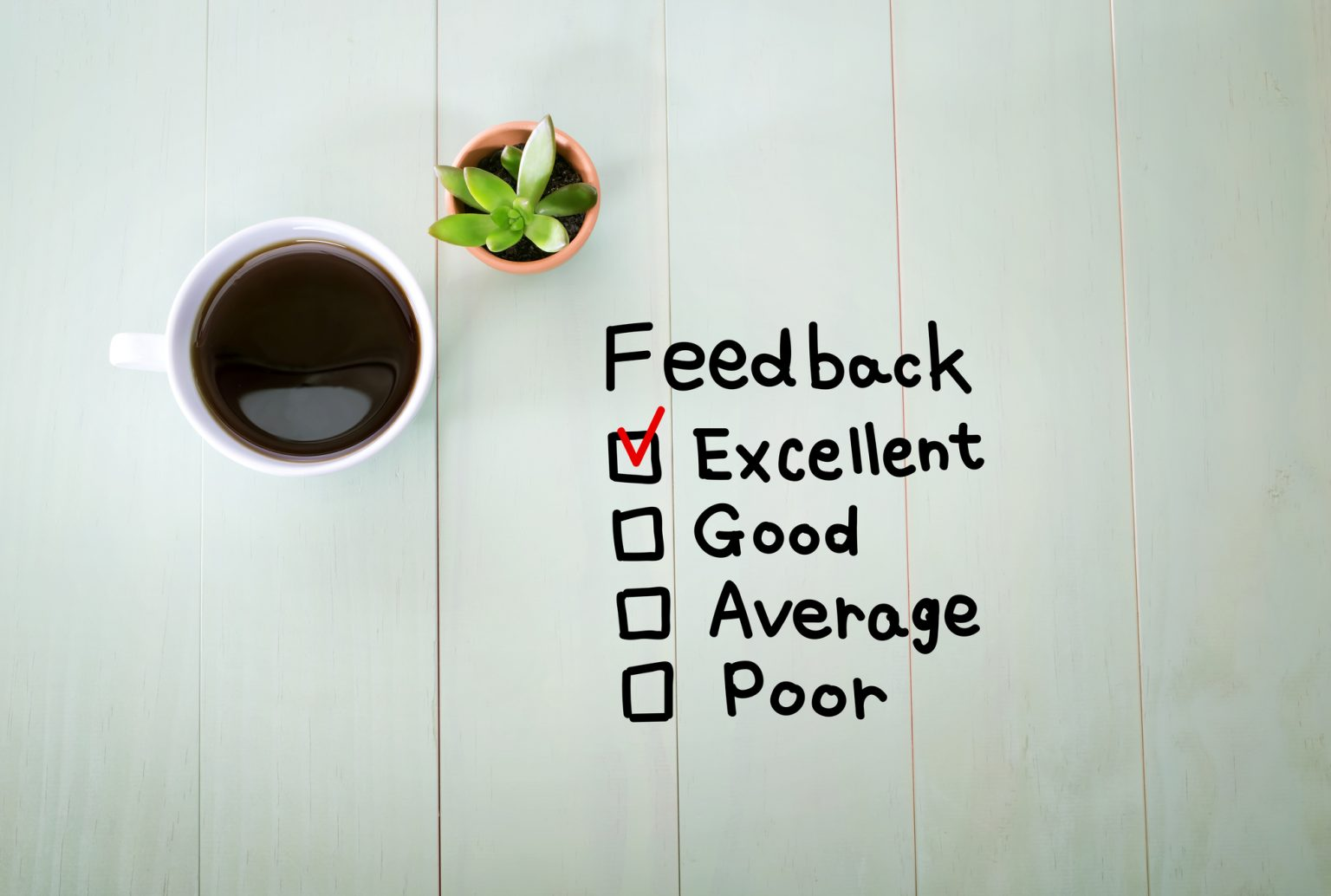 Feedback concept with a cup of coffee on a pastel green wooden table